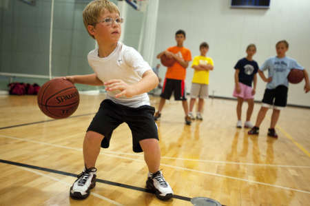 "Jake May/Staff Photographer Brendan Zeien, 9, of Mount Pleasant demonstrates good dribbling form in front of about 25 other students for the Youth Basketball Development Camp on Tuesday at Morey Courts Recreational Center. ""I usually practice a lot of dribbling, and when I do, I have to keep my stance. Once you have that, then you can start turning your head,"" he said. ""I love basketball because you can shoot, you can pass and it's just so much fun. It makes me stronger and stronger every day."""